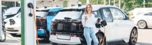 Mujer cargando su coche eléctrico en una estación de carga.